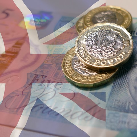 coins and banknote with UK flag
