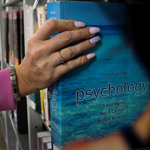 student holding psychology book in library