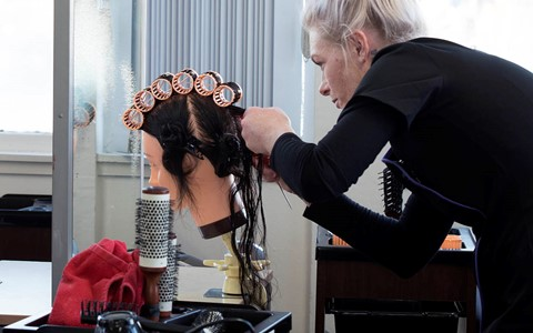 hairdressing student working with model head