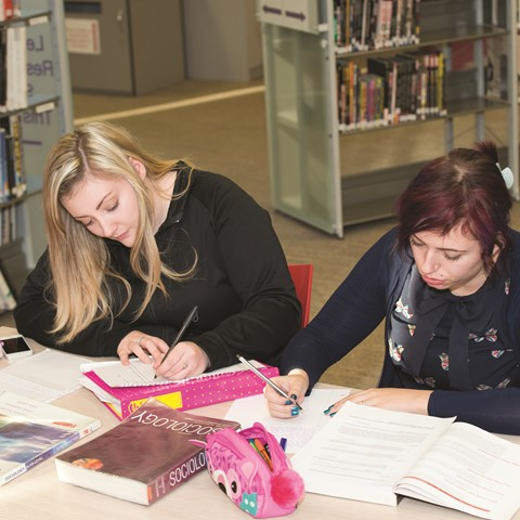 Two girls in library, writing.