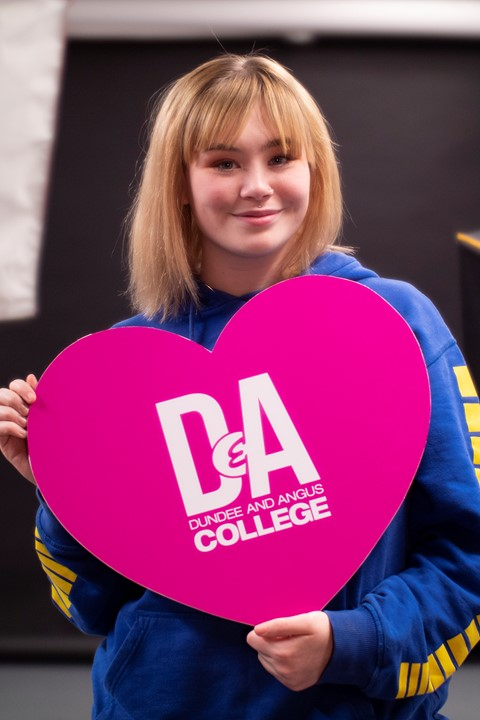student holding a heart with D&A logo