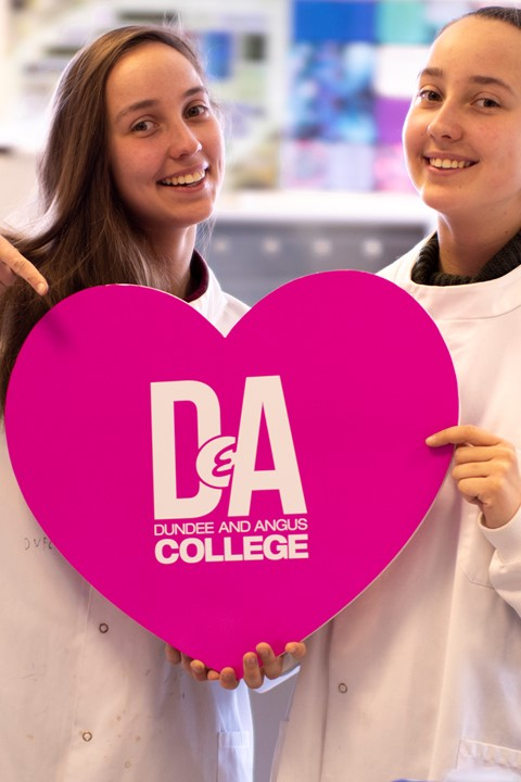 students holding a heart with D&A logo