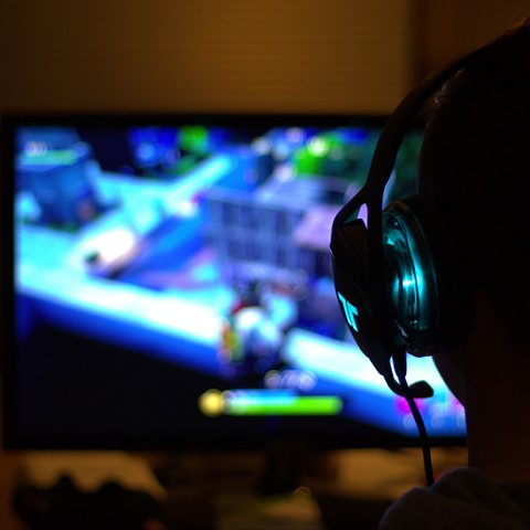 person with headset playing computer game