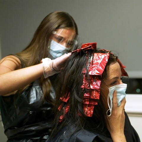 Hairdresser dying customers hair