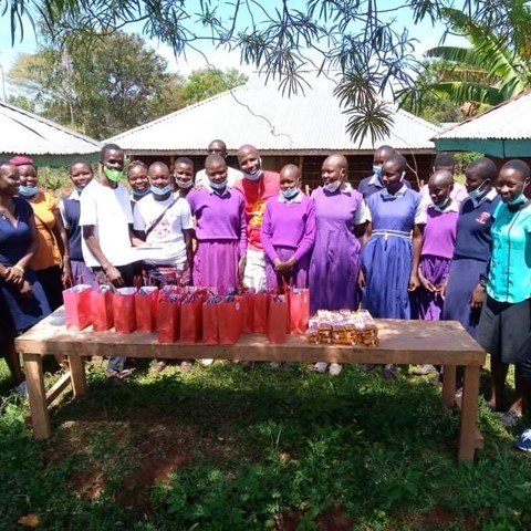 A group of students from a school in Kenya receiving free period products from the college