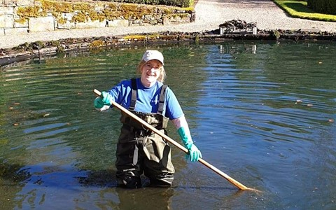 Charlotte Paterson cleaning out a pond
